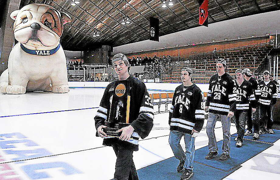 The Yale hockey team, led by goalie Jeff Malcolm, leaves Ingalls Rink with the NCAA national championship trophy after a ceremony for the returning champions in April. Photo: Peter Casolino — Register