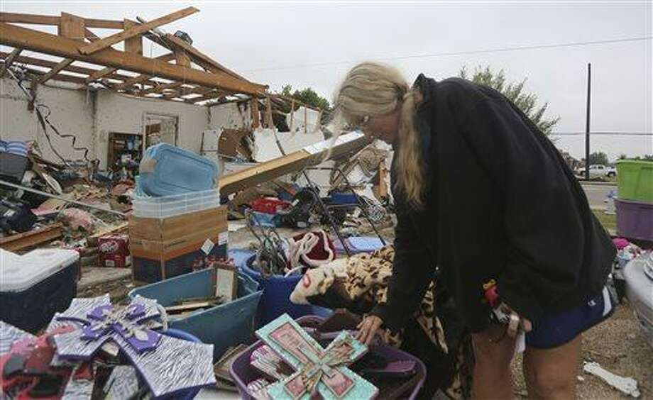 Lisa Montgomery looks at crosses she salvaged from her home that was destroyed by a tornado in Cleburne, Texas, Thursday, May 16, 2013.  Ms. Montgomery rode out the twister the night before in her bathtub with her 10-year-old son and is salvaging items with friends and family helping.  Ten tornadoes touched down in several small communities in Texas overnight, leaving at least six people dead, dozens injured and hundreds homeless. Emergency responders were still searching for missing people Thursday afternoon. (AP Photo/LM Otero) Photo: ASSOCIATED PRESS / AP2013