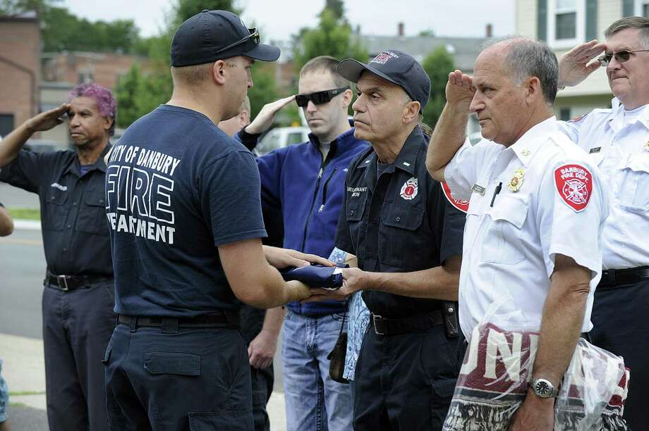 Firefighter Scott Yaglowski presents Lt. Albert Mion with an American flag which flew over the fire department headquarters on New Street on Tuesday. The flag ceremony was held Tuesday, July 25, 2017, for Lt.  Mion, of the Danbury Fire Department who is retiring just shy of 34 years of service. Photo: Carol Kaliff / Hearst Connecticut Media / The News-Times