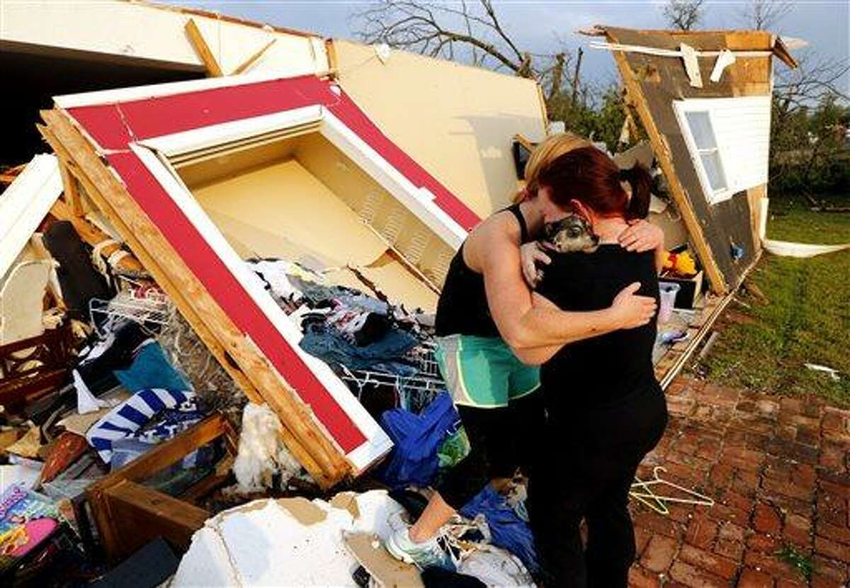 Alli Christian, left, returns Jessica Wilkinson's dog Bella to her after finding her among the wreckage of Wilkinson's home shortly after a tornado struck near 156th street and Franklin Road on Sunday, May 19, 2013 in Norman, Okla. No one was in the home when the storm struck. (AP Photo/The Oklahoman, Steve Sisney)