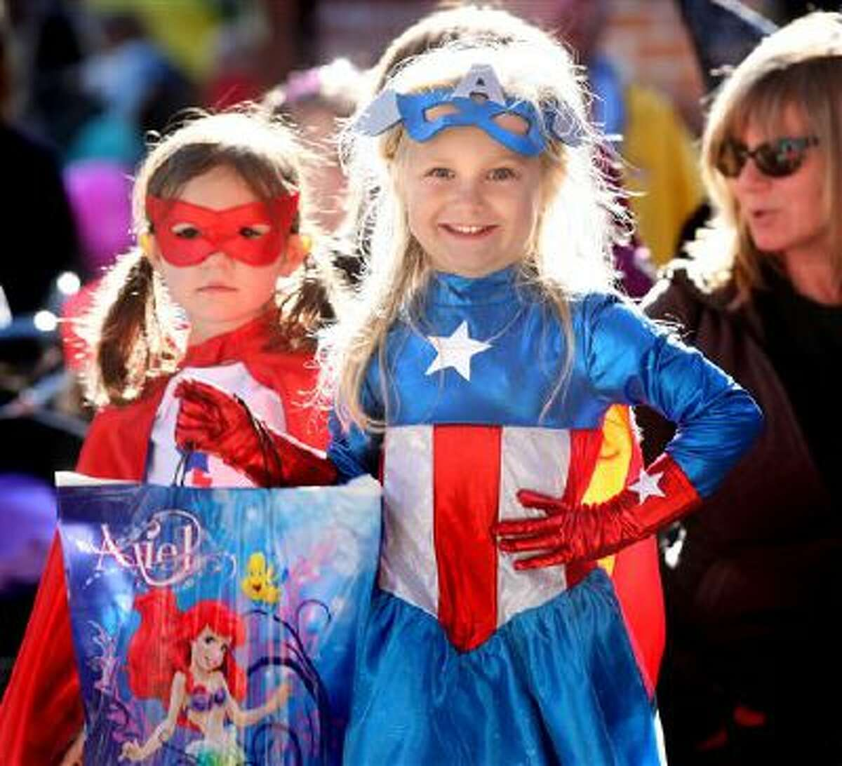 Captain America Zoey Creswell, 4, and her superhero/princess cousin Kambree Caton, 3, both of Winchester, Va., participate in the Old Town Spooktacular event where store owners give candy to trick-or-treaters. (AP Photo, The Winchester Star, Jeff Taylor)