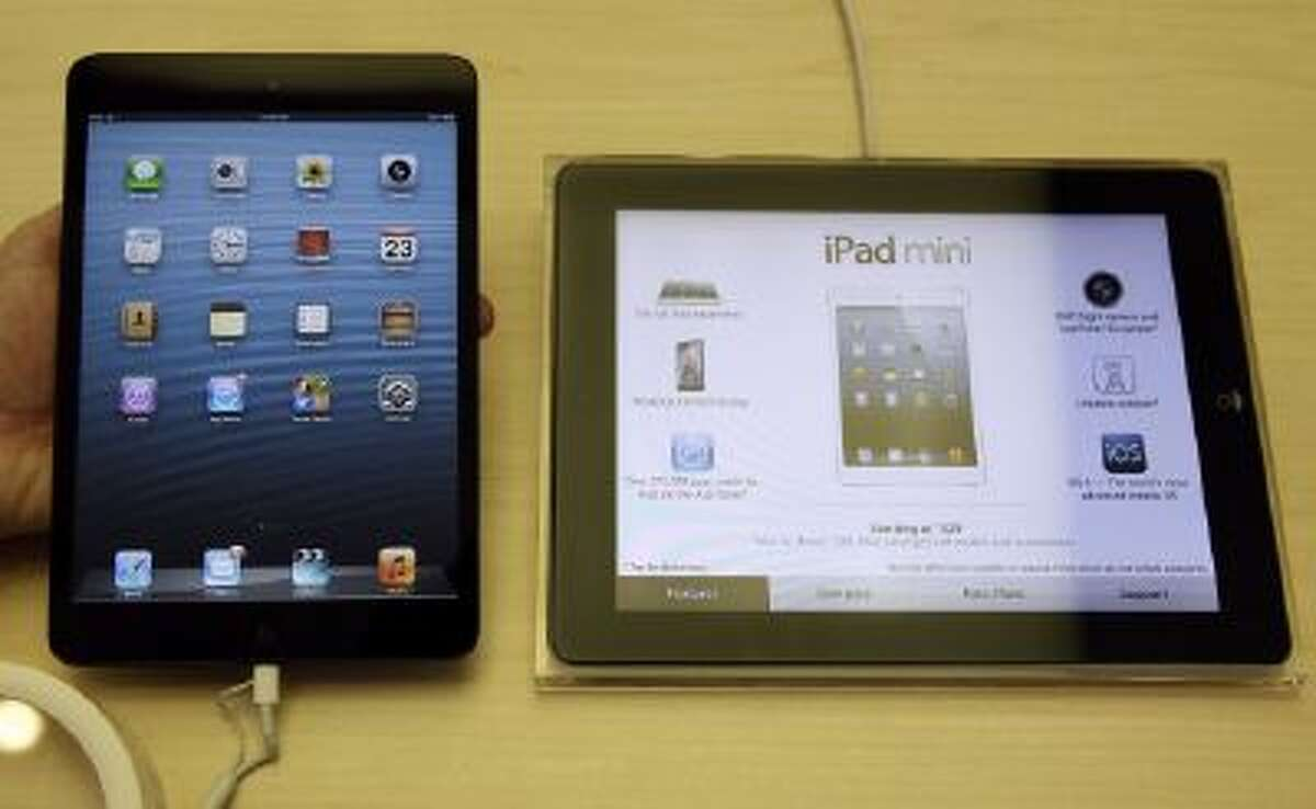 An Apple iPad mini, left, is held next to an iPad at an Apple store in San Francisco, Friday, Nov. 23, 2012.
