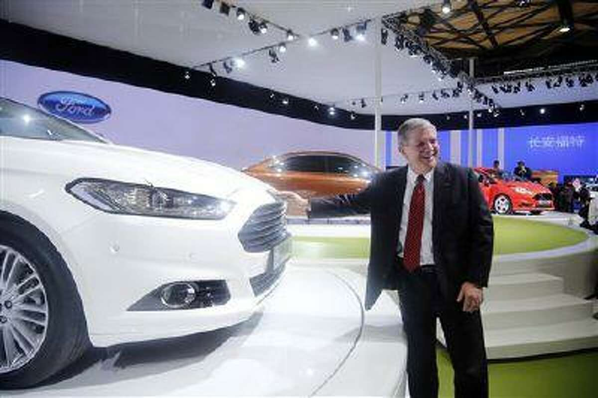 In this photo taken April 20, 2013, David Schoch, Ford Motor Company group vice president and president, Asia Pacific, poses for photos by Ford's new Mondeo car at the Shanghai Auto Show in Shanghai, China. (AP Photo)