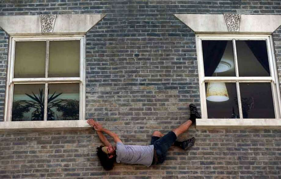 A visitor enjoys an art installation by Argentine artist Leandro Erlich in east London, Tuesday, July 9, 2013. Internationally known for his three-dimensional visual illusions, Erlich has been commissioned to create a new installation in Dalston area of the capital. Resembling a theatre set, the detailed facade of a Victorian terraced house, recalling those that once stood on the street, lies horizontally on the ground with mirrors positioned overhead. The reflections of visitors give the impression they are standing on, suspended from, or scaling the building. (AP Photo/Lefteris Pitarakis) Photo: ASSOCIATED PRESS / AP2013