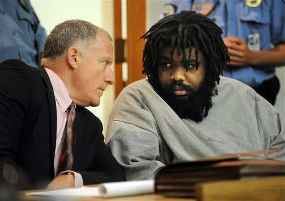 Defendant Tyree Lincoln Smith, right, makes eye contact with his attorney, public defender Joseph Bruckmann, after a three-judge panel found him not guilty by reason of insanity in the death of a homeless man he admitted to killing and partially eating, Tuesday, July 9, 2013 in state Superior Court in Bridgeport, Conn. (AP Photo/The Connecticut Post, Brian A. Pounds, Pool) Photo: AP / Pool The Connecticut Post
