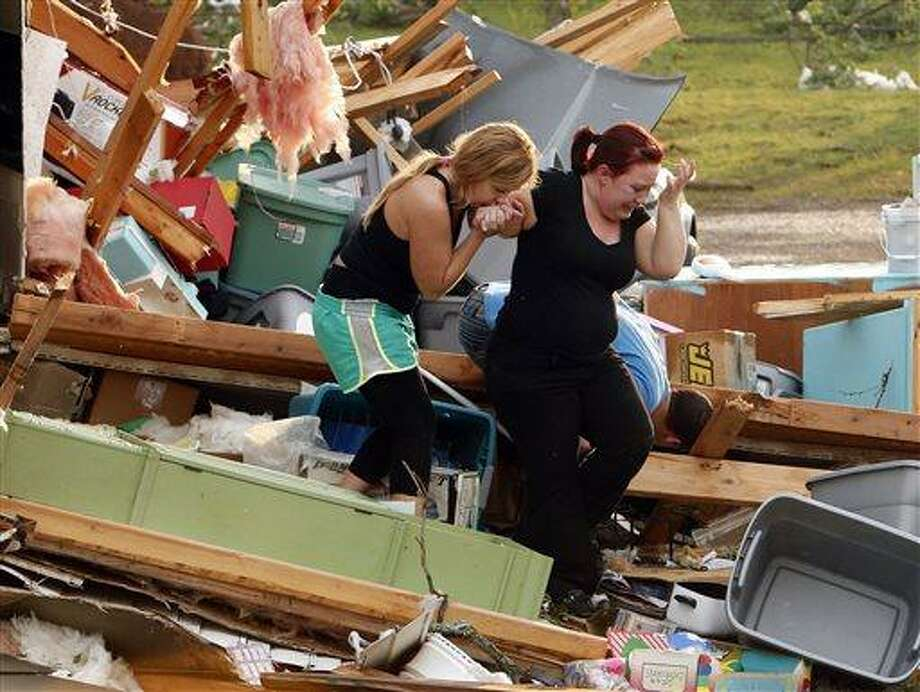 Alli Christian, left, helps Jessica Wilkinson as she looks for her dog Bella after Wilkinson returned to find her home near 156th street and Franklin Road destroyed by a tornado, Sunday, May 19, 2013, in Norman, Okla. (AP Photo/The Oklahoman, Steve Sisney) Photo: AP / The Oklahoman