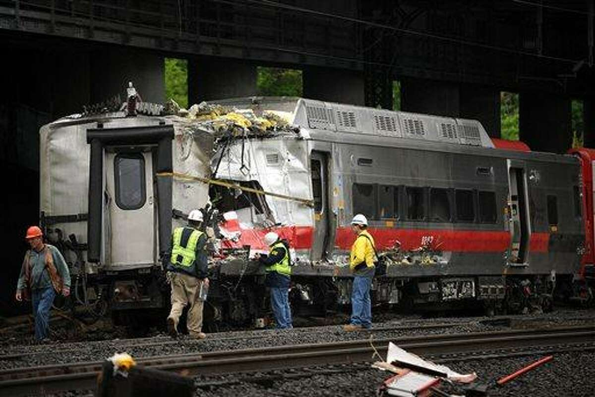 Metro-North employees work at the site of Friday's train derailment in Bridgeport. Conn. on Sunday, May 19, 2013. Crews will spend days rebuilding 2,000 feet of track, overhead wires and signals following the collision between two trains Friday evening that injured 72 people, Metro-North President Howard Permut said Sunday. (AP Photo/The Connecticut Post,Brian A. Pounds ) MANDATORY CREDIT