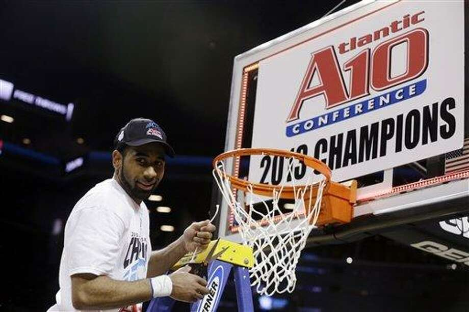 FILE - In this March 17, 2013, file photo, Saint Louis' Kwamain Mitchell cuts down part of the net after an NCAA college basketball game against Virginia Commonwealth in the championships of the Atlantic 10 Conference tournament in New York. Saint Louis won 62-56. After running into New York traffic and without any fuss _ because that is the Saint Louis way _ the team bus pulled off the road and into the parking lot at Best Buy to find out where they were seeded (No. 4 in the Midwest) and who they were matched against (New Mexico State). (AP Photo/Seth Wenig, File) Photo: ASSOCIATED PRESS / A2013