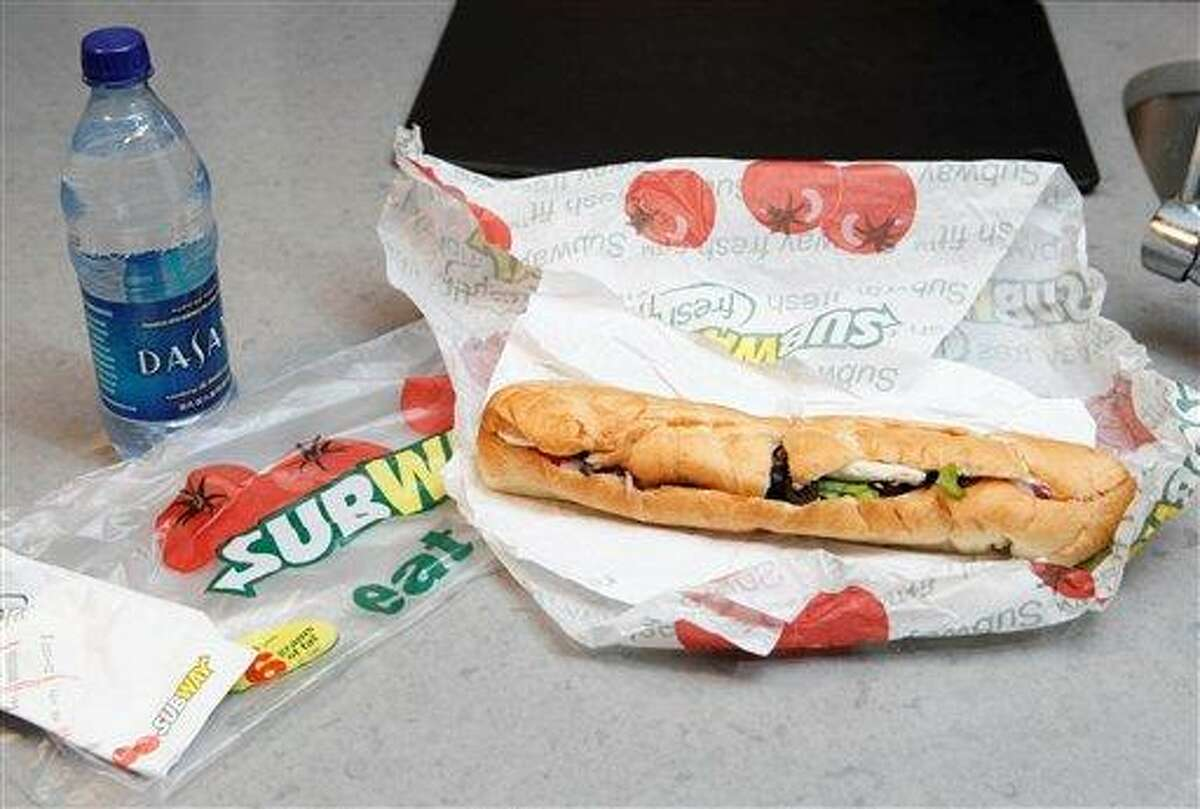 FILE - This Aug. 11, 2009, file photo, shows a chicken breast sandwich and water from subway on a kitchen counter in New York. Subway, the world's largest fast food chain, is facing criticism after an Australian man posted a picture on the company's Facebook page on Jan. 16, 2013, of one of its famous sandwiches next to a tape measure that seems to shows it's not as long as promised. (AP Photo/Seth Wenig, File)