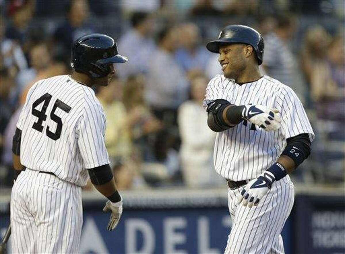 New York Yankees left fielder Zoilo Almonte (45) greets New York Yankees Robinson Cano after Cano hit a third-inning, three-run home run in a baseball game Kansas City Royals, Wednesday, July 10, 2013, in New York. (AP Photo/Kathy Willens)