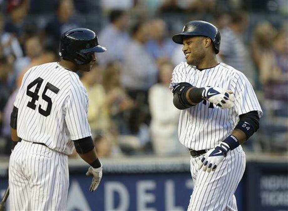 New York Yankees left fielder Zoilo Almonte (45) greets New York Yankees Robinson Cano after Cano hit a third-inning, three-run home run in a baseball game Kansas City Royals, Wednesday, July 10, 2013, in New York. (AP Photo/Kathy Willens) Photo: AP / AP