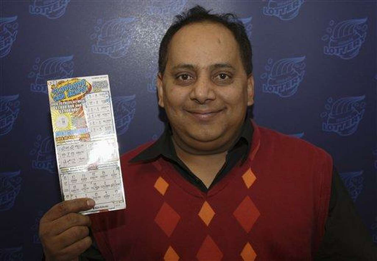FILE - This undated file photo provided by the Illinois Lottery shows Urooj Khan, 46, of Chicago's West Rogers Park neighborhood, posing with a winning instant lottery ticket. On Friday, Jan 11, 2013, a Cook County judge granted authorities permission to exhume the body of the Chicago lottery winner who was fatally poisoned with cyanide just as he was about to collect his $425,000 payout. His July 20 death was initially ruled a result of natural causes. (AP Photo/Illinois Lottery, File)