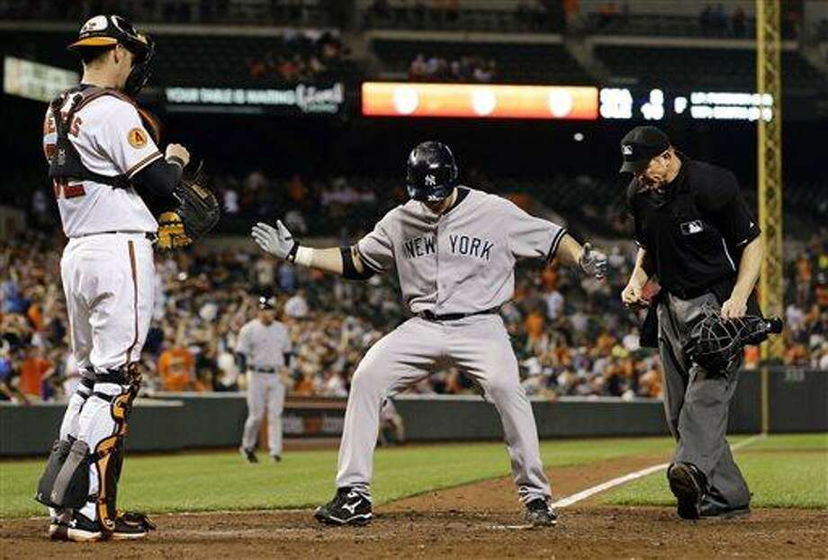 New York Yankees designated hitter Travis Hafner, center, crosses home plate after hitting a solo home run in the ninth inning of a baseball game against the Baltimore Orioles in Baltimore, Monday, May 20, 2013. New York won 6-4 in 10 innings. (AP Photo/Patrick Semansky) Photo: AP / AP