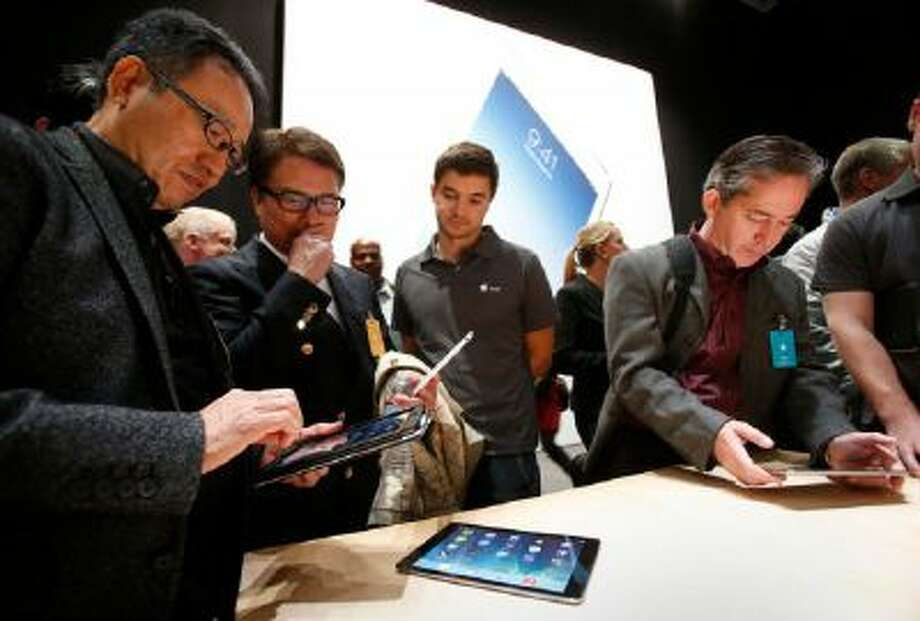 """Tech reporters paw Apple's new iPad models Tuesday Oct. 22, 2013 in San Francisco, Calif., after the Cupertino-based company announced its latest release, the iPad Air, a 10-inch tablet with a thinner body and a new iPad Mini with high-definition """"Retina"""" display."""