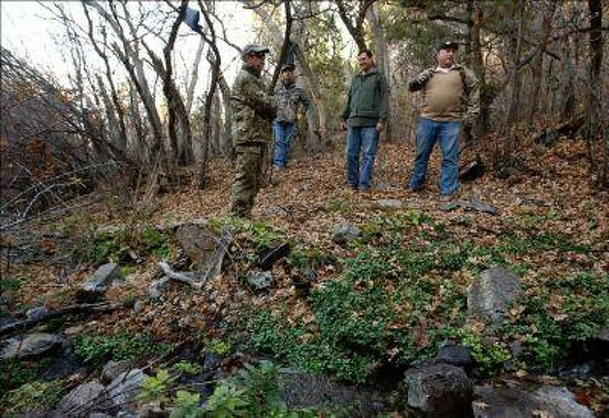 DEA and Narcotics Task Force agents, Rodney Holliday, Brian Lacy, Cliff Lark and Brian Bairett stand near the water source that fed a marijuana grove of over 4,200 plants last year in Iron County. Clothing, boots, backpacks and hygiene items littered the area. (Leah Hogsten, Salt Lake Tribune file photo)