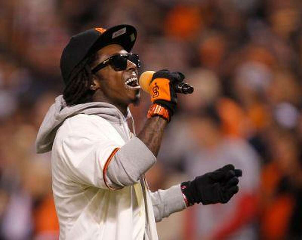 """Rapper Lil Wayne sings """"Take Me Out To The Ball Game"""" during the seventh inning stretch in Game 6 of the MLB NLCS playoff baseball series between the St. Louis Cardinals and the San Francisco Giants in San Francisco."""