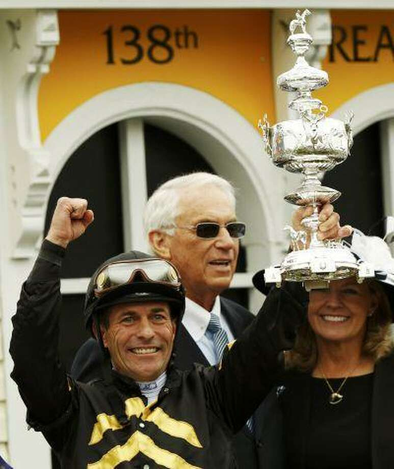 Jockey Gary Stevens (L) holds the trophy beside trainer D. Wayne Lukas (C) after their horse Oxbow took first place at the 138th running of the Preakness Stakes at Pimlico Race Course in Baltimore, Maryland May 18, 2013. Photo: REUTERS / X00157