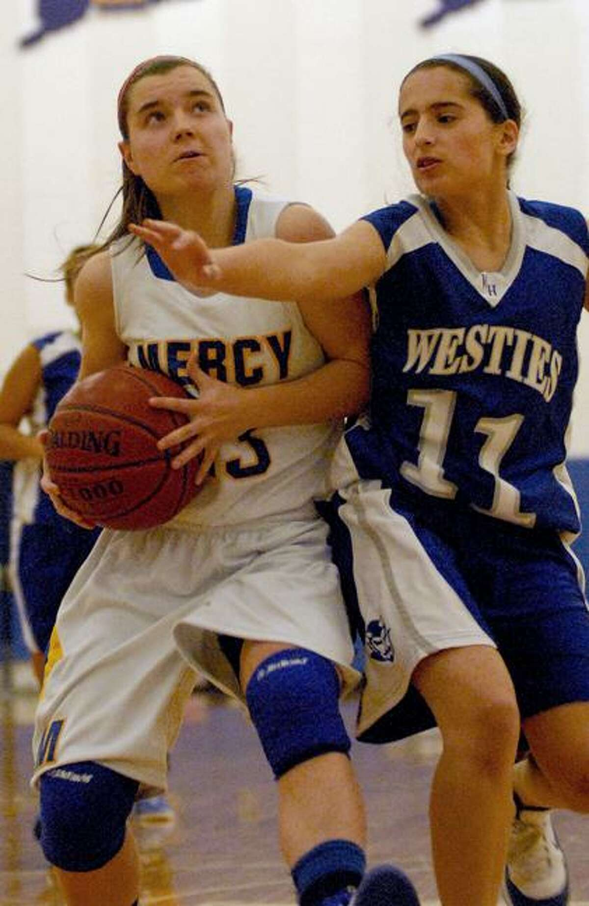 Catherine Avalone/The Middletown PressMercy senior captain Maria Weselyj drives to the hoop as West Haven's Amanda Martino defends. Weselyj surpassed 1,000 career points Friday night as the Tigers defeated the Westies 73-32 in Middletown.