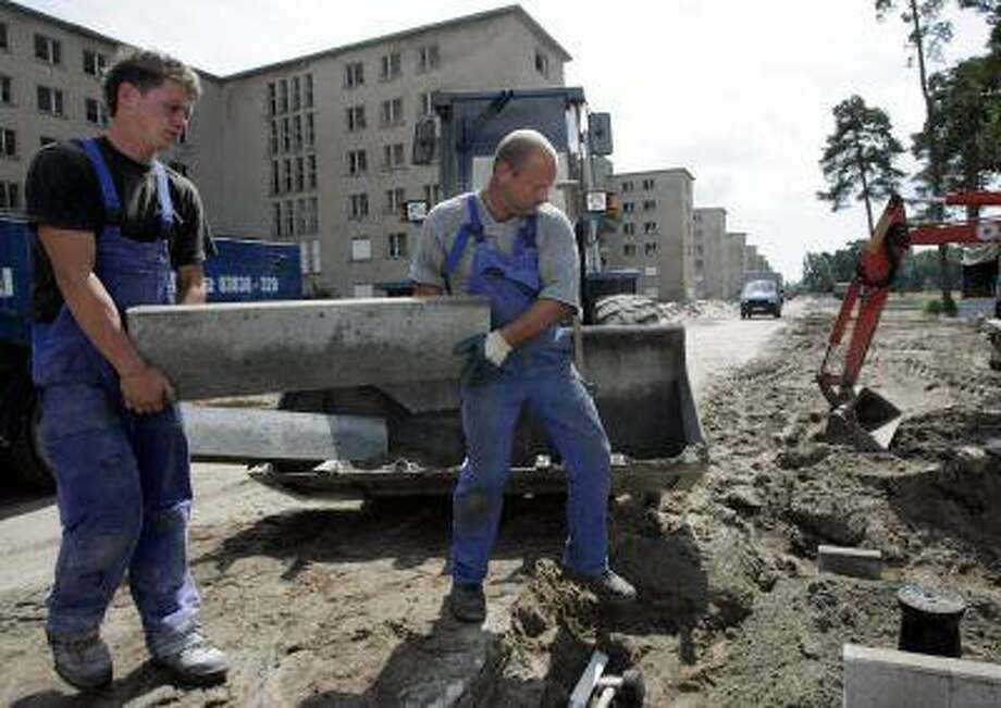 Building workers fix up the area set to be a new camping-site 24 July 2007 next to the 4.5 kilometres long so-called 'colossus of Ruegen'-complex in Prora on the Baltic Sea island Ruegen. Photo: AFP/Getty Images / 2007 AFP