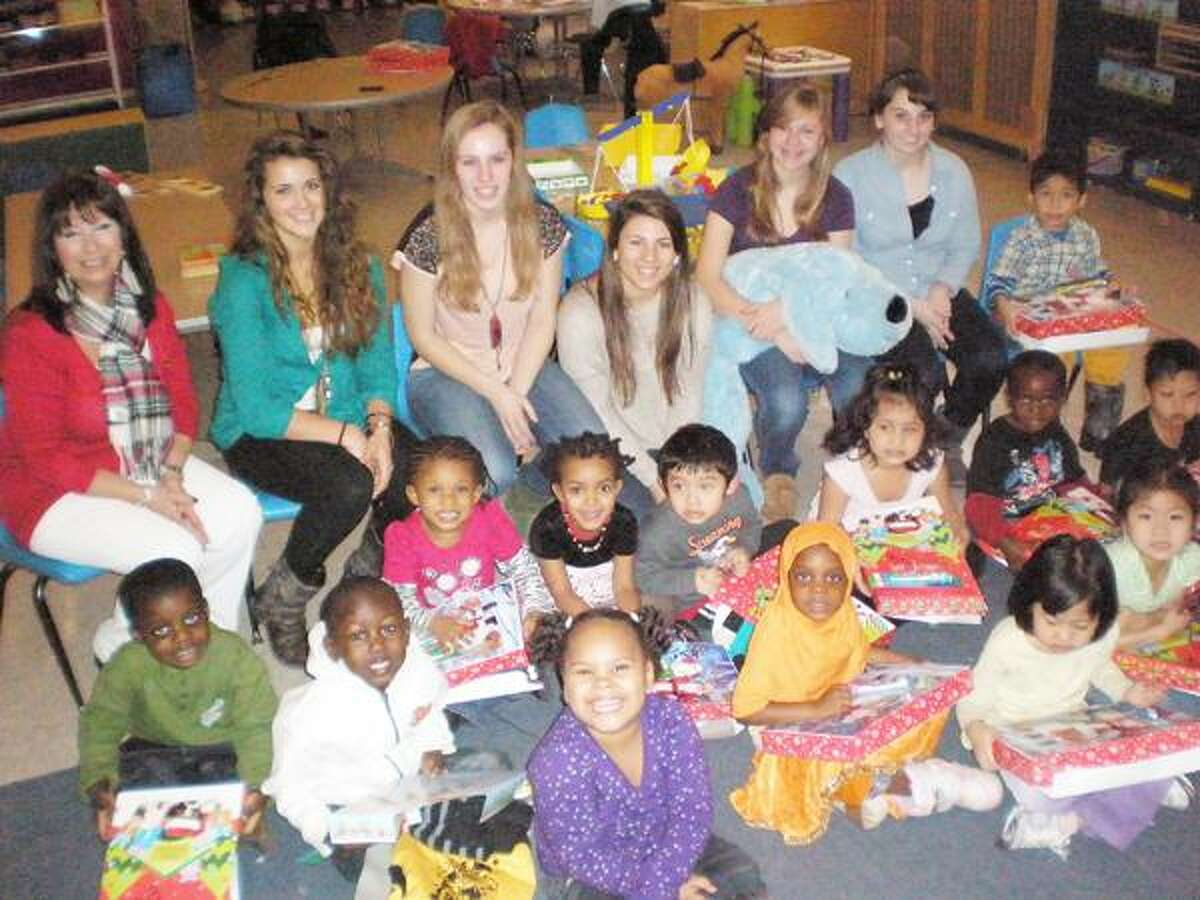 Photo Courtesy ONEIDA Z CLUB Members of the Oneida High Scool Z Club sit with students at CYO Pre-K in Syracuse.