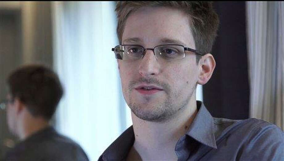 This photo provided by The Guardian Newspaper in London shows Edward Snowden, who worked as a contract employee at the National Security Agency, on Sunday, June 9, 2013, in Hong Kong. NSA leaker Edward Snowden claims the spy agency gathers all communications into and out of the U.S. for analysis, despite government claims that it only targets foreign traffic. (AP Photo/The Guardian, Glenn Greenwald and Laura Poitras) Photo: AP / The Guardian