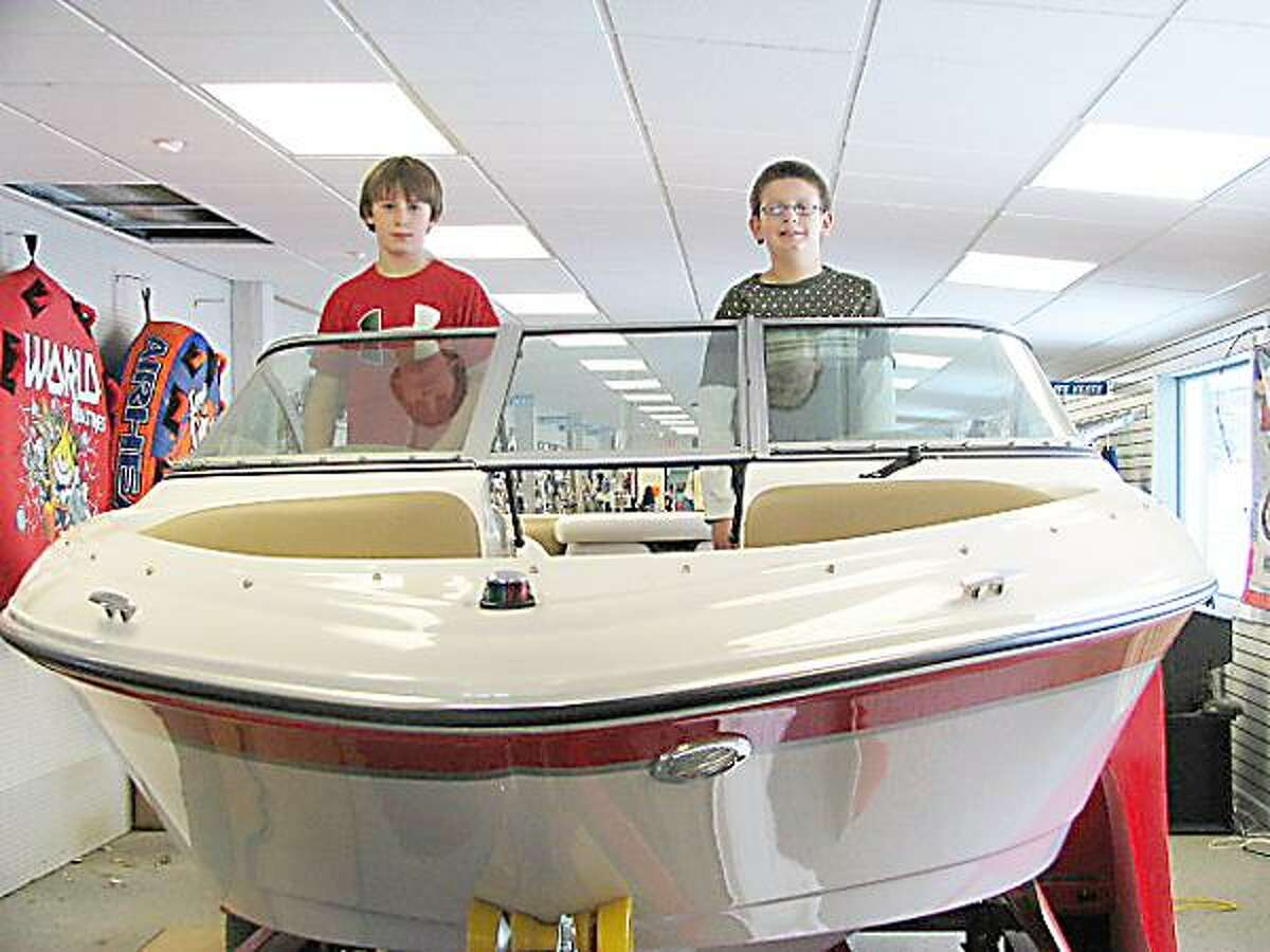 Photo Courtesy COOPER'S MARINA Jacob, left, and Adam Cooper, seen here at Cooper's Marina in Baldwinsville, earned their Young Boater Safety Certificates at the 2010 Central New York Boat Show.