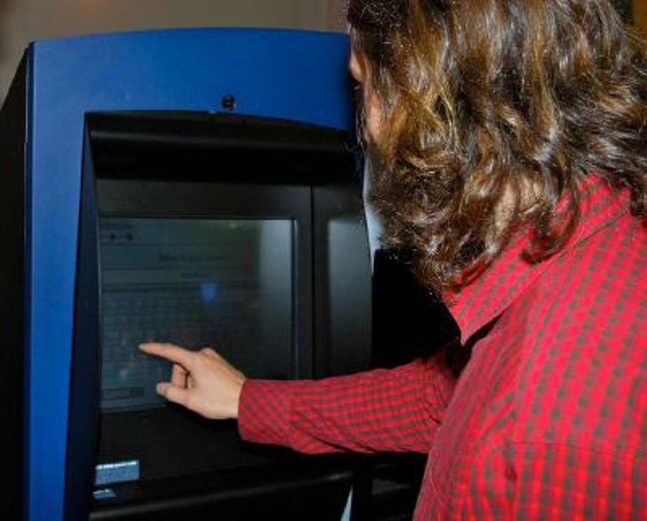 Adam Soltys, co-founder of a bit coin co-operative in Vancouver, swaps Canadian currency for bitcoins using the new bitcoin ATM installed at the Waves coffee shop in the city's downtown on October 29, 2013.