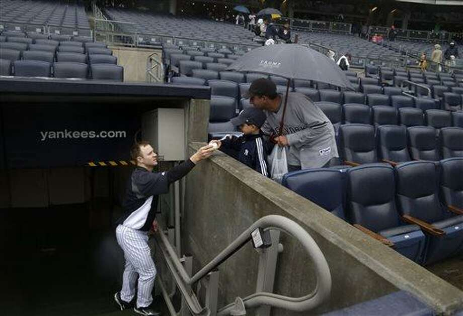 New York Yankees' David Adams, left, hands a ball to fans after the game was postponed at Yankee Stadium Sunday, May 19, 2013, in New York. The game between the Toronto Blue Jays and the New York Yankees was postponed due to wet weather.(AP Photo/Seth Wenig) Photo: AP / AP