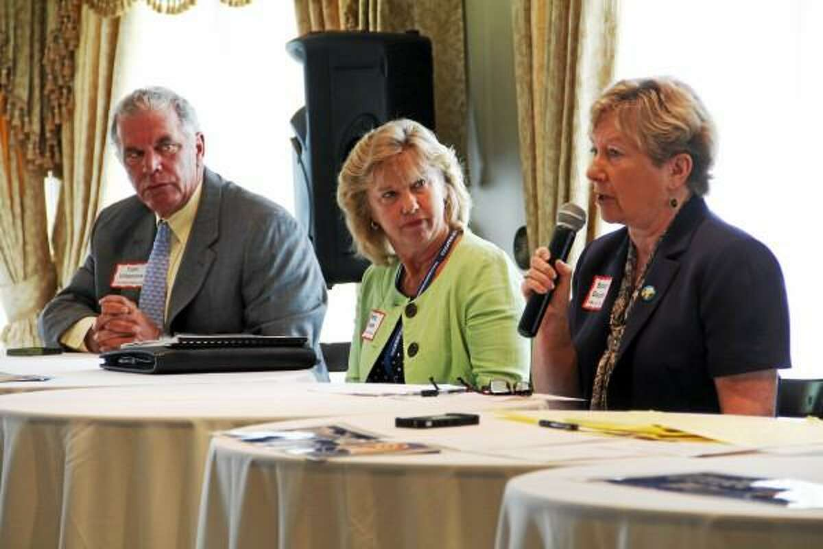 Tom Villanova and Mary Bevan listen to Barbara Douglass (mic in hand) as she responds to a discussion question during the the United Way of Northwest Connecticut's Community Leaders Breakfast at Torrington Country Club on Wednesday, July 10, 2013. The event addressed poverty rates in the northwest corner, and five panelists, three of them pictured here, were asked to offer responses to questions relating to ending poverty in the state. Esteban L. Hernandez Register Citizen