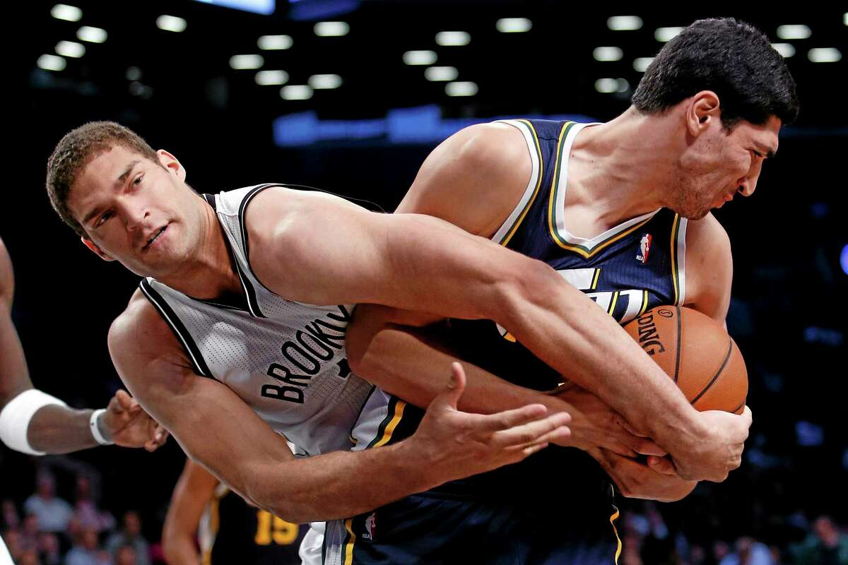 The Nets' Brook Lopez, left, fights for possession with the Jazz's Enes Kanter during Tuesday's game in Brooklyn.