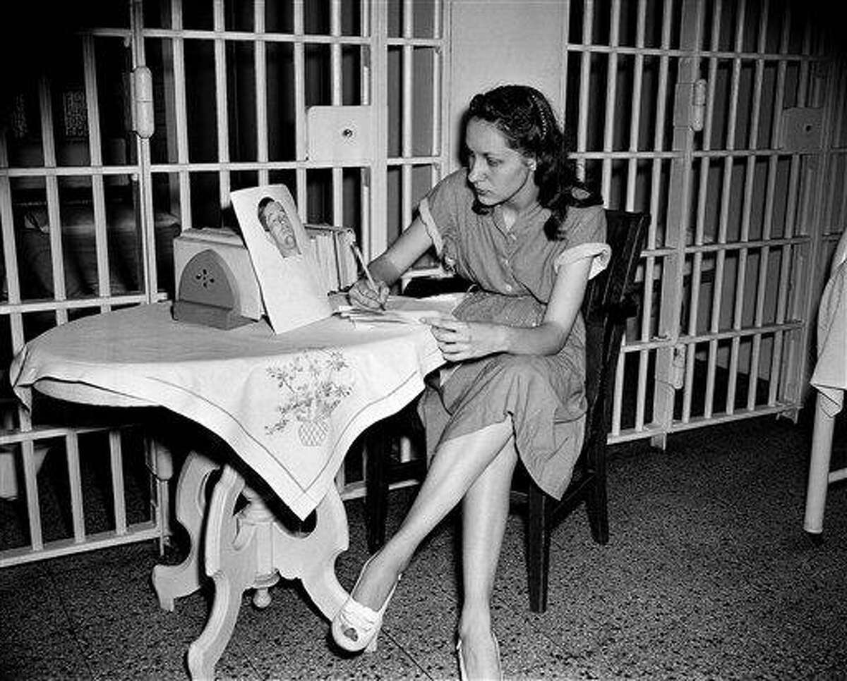 FILE - In this June 18, 1949 file photo, Ruth Steinhagen, 19, held in the shooting of Philadelphia Phillies first baseman Eddie Waitkus at a Chicago hotel on June 14, 1949, writes notes for her life history in Cook County Jail in Chicago. At the table she has a photograph of Waitkus taken June 17 in the hospital where he was recovering from a bullet wound. Steinhagen died of natural causes at 83 in late December 2012. Her death is the final chapter in one of the most sensational and bizarre criminal cases in Chicago history that made headlines around the country. She was the inspiration for Bernard Malamud's novel 'The Natural' and the 1984 movie starring Robert Redford. (AP Photo/File)