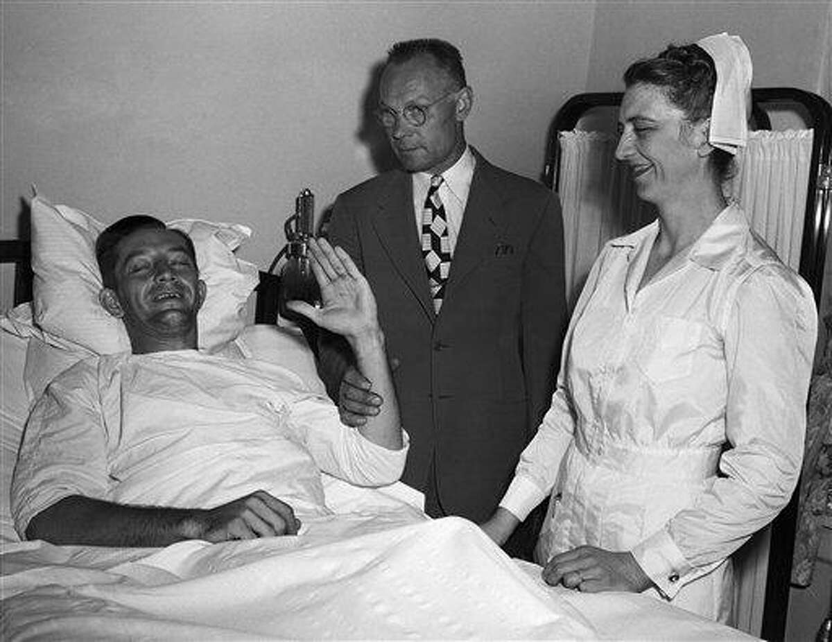 FILE - In this June 17, 1949 file photo, Philadelphia Phillies first baseman Eddie Waitkus smiles from his bed in Illinois Masonic Hospital in Chicago as his father, Stephen, holds up his arm for an attempted wave. Waitkus was shot and seriously wounded June 14 in a Chicago hotel by 19-year-old Ruth Steinhagen. Steinhagen died of natural causes at 83 in late December 2012. Her death is the final chapter in one of the most sensational and bizarre criminal cases in Chicago history that made headlines around the country. She was the inspiration for Bernard Malamud's novel 'The Natural' and the 1984 movie starring Robert Redford. (AP Photo/File)