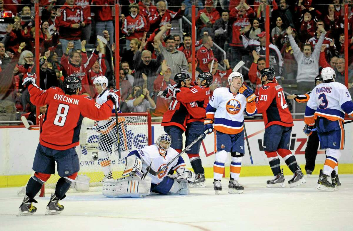Capitals center Marcus Johansson (90) celebrates his goal with Nicklas Backstrom (19), Alex Ovechkin (8) and Troy Brouwer (20) as New York Islanders goalie Evgeni Nabokov looks on during the second period of Tuesday's game in Washington. Also seen are Islanders center Casey Cizikas (53) and Travis Hamonic (3).
