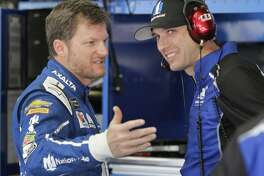 FILE - In this May 27, 2017, file photo, Dale Earnhardt Jr., left, talks with crew chief Greg Ives during practice for a NASCAR Cup series auto race at Charlotte Motor Speedway in Concord, N.C. Before Dale Eanrhardt Jr. calls it a career and starts calling races for NBC, he'd like to salvage a few positive memories from this season.And he'd like fans to quit ripping his embattled crew chief. (AP Photo/Chuck Burton, File)