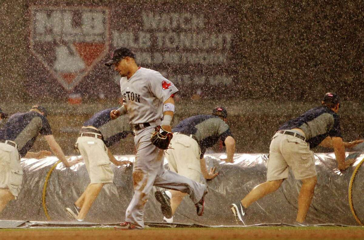 Boston Red Sox right fielder Shane Victorino (18) runs to the dugout as grounds crew tarp the field during a rain delay called during the seventh inning of a baseball game against the Minnesota Twins, Sunday, May 19, 2013, in Minneapolis. (AP Photo/Genevieve Ross)