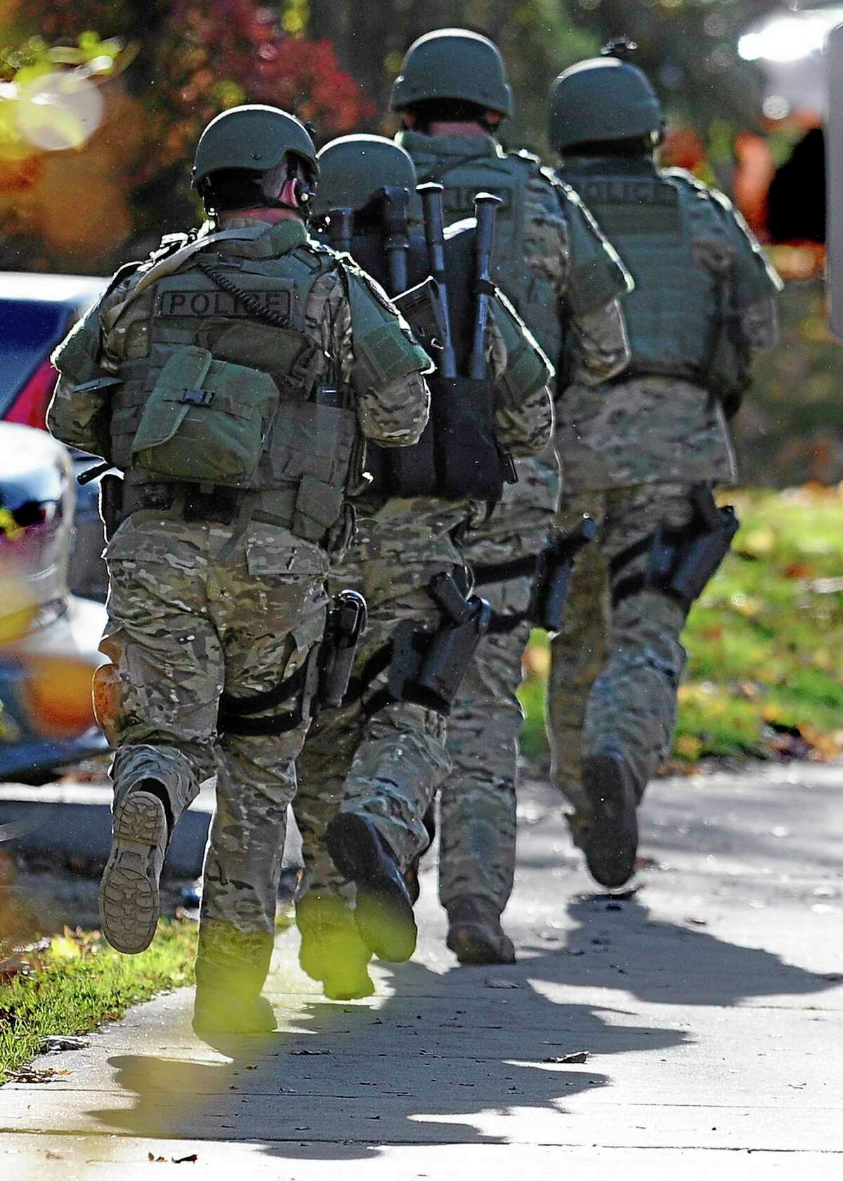 """SWAT move in a line on the campus of Central Connecticut State University, Monday, Nov. 4, 2013, in New Britain, Conn. An armed man was spotted on the campus of Central Connecticut State University, prompting a schoolwide lockdown and warnings for students to stay away from windows as police SWAT teams swarmed the area. University spokesman Mark McLaughlin said, """"Somebody was seen either with a gun or was thought to have a gun."""" (AP Photo/Jessica Hill)"""
