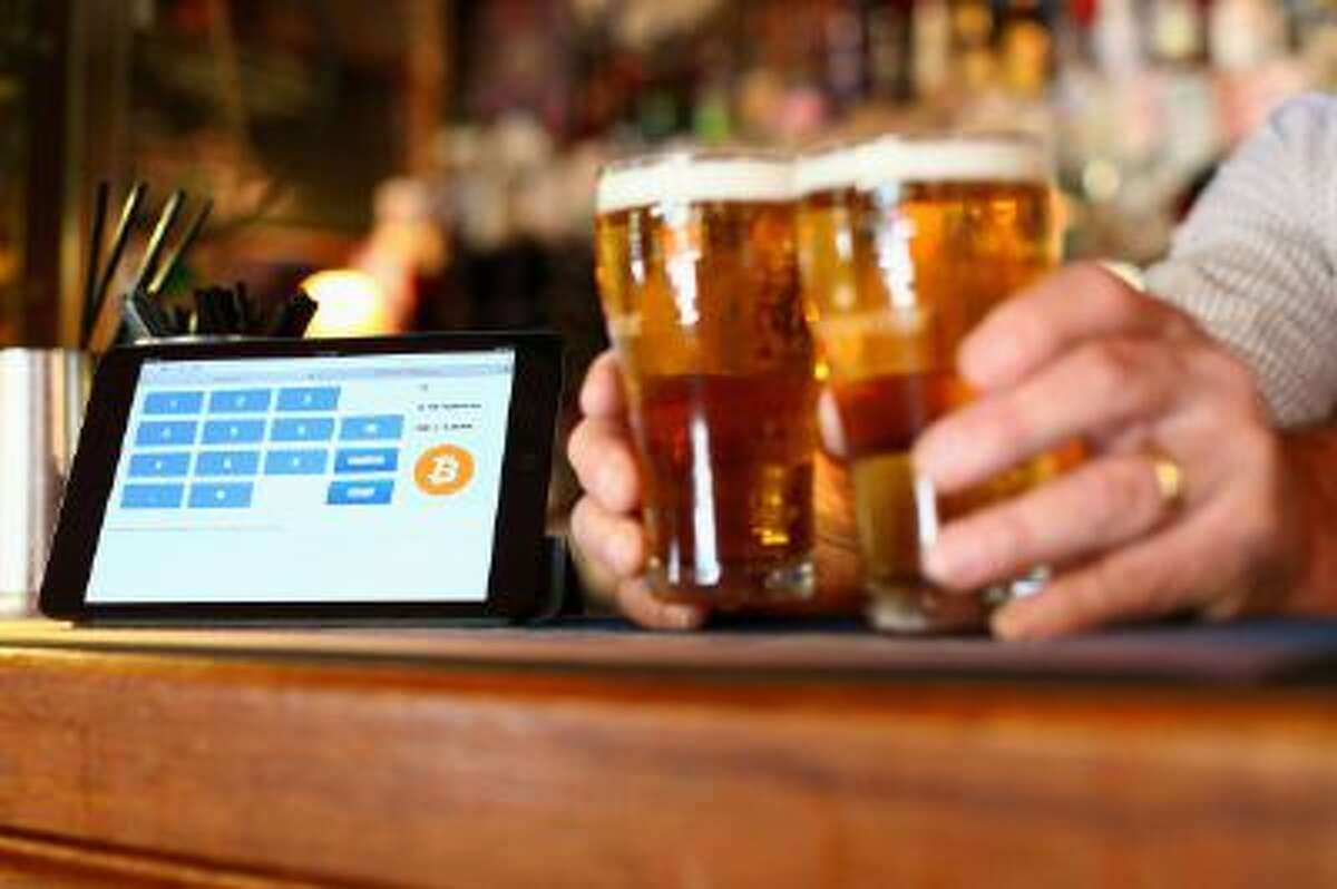 In this photo illustration, a terminal to accept payments using bitcoins is shown on the bar at the Old Fitzroy pub in Sydney, Australia.