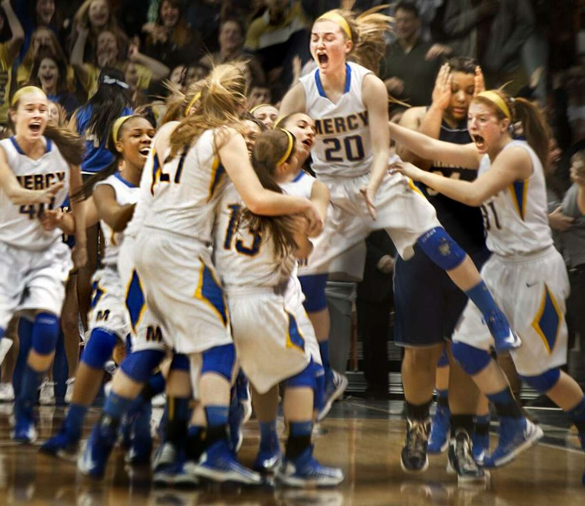 Sports-Olivia Levey walks through Mercy players celebrating the game winning shot of Maria Weselyj in the CIAC State Finals. Melanie Stengel/Register
