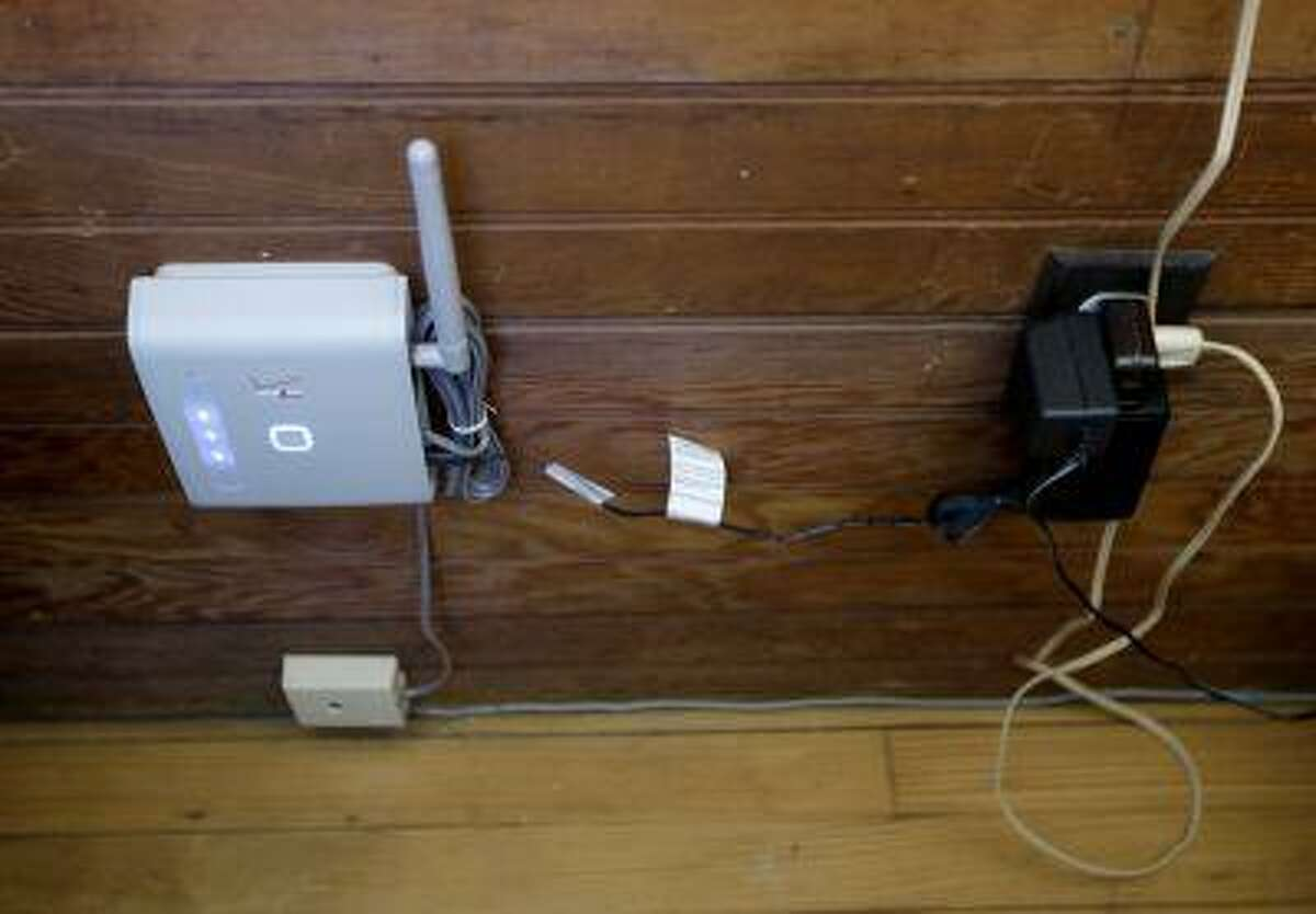 In this Friday, May 31, 2013 photo, a wireless device that can be connected to a home phone for service is seen inside Robert Post's home, in Mantoloking, N.J., which was flooded during Superstorm Sandy last year. Post has a pacemaker that needs to be checked once a month by phone, but the phone company refuses to restore the area's landlines after they were damaged by the storm. Verizon doesn't want to replace washed-away lines and waterlogged underground cables because phone lines are outdated, it says. Meanwhile, the company is offering the wireless device, but the system does not work with pacemakers or fax machines. (AP Photo/Julio Cortez)