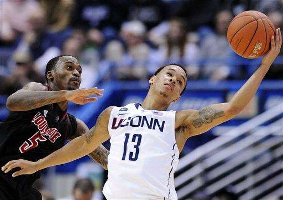 Louisville's Kevin Ware, left, and Connecticut's Shabazz Napier scramble for a loose ball during the second half their NCAA college basketball game in Hartford, Conn., Monday, Jan. 14, 2013. Louisville won 73-58. (AP Photo/Fred Beckham) Photo: ASSOCIATED PRESS / AP2013