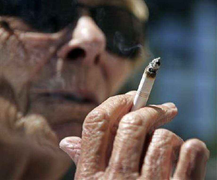 FILE - In this June 11, 2007 file photo, Helen Heinlo smokes outside of a coffee shop in Belmont, Calif. Some smokers trying to get coverage in 2014 under President Barack Obama's health care law may get a break from tobacco-use penalties that could have made their premiums unaffordable. The Obama administration _ in yet another health care overhaul delay _ has quietly notified insurers that a computer system glitch will limit penalties that the law says the companies may charge smokers. A fix will take at least a year to put in place. (AP Photo/Paul Sakuma, File) Photo: AP / AP