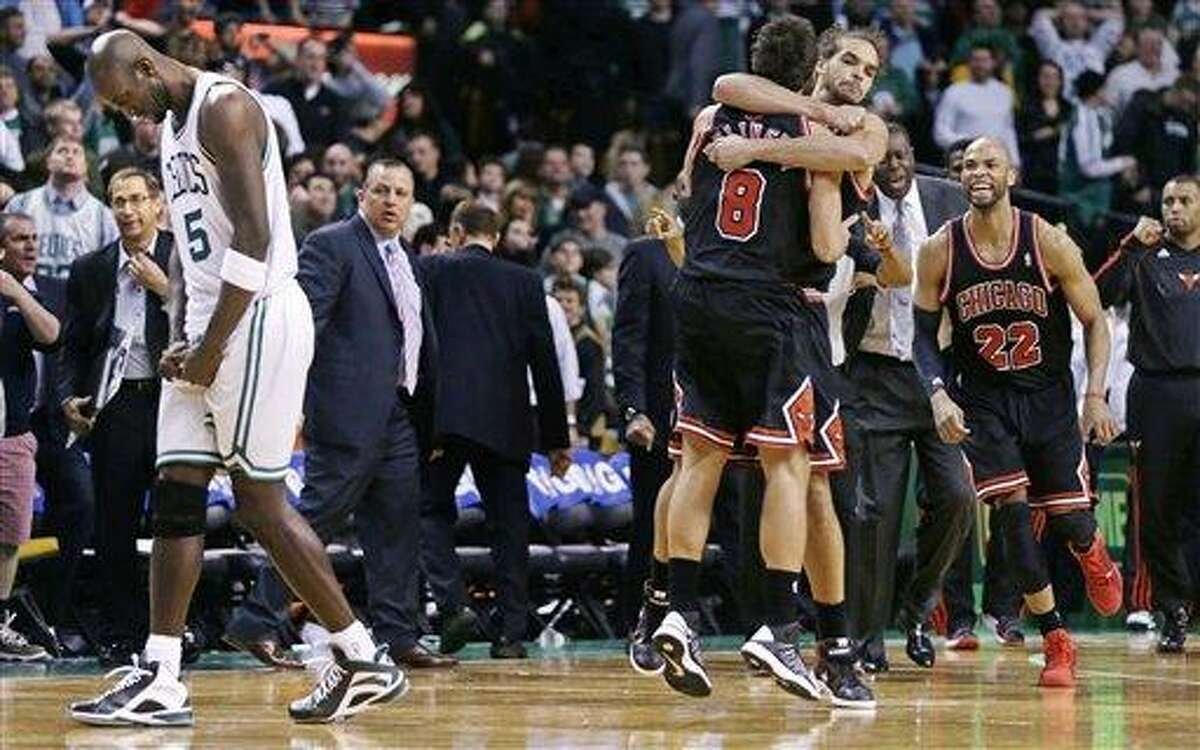 As Boston Celtics forward Kevin Garnett, left, walks off the court, Chicago Bulls guard Marco Belinelli (8) is congratulated by teammate Joakim Noah taking an overtime win in an NBA basketball game in Boston Friday, Jan. 18, 2013. Belinelli hit the go ahead basket less than 5 seconds on the clock. The Bulls beat the Celtics 100-99. (AP Photo/Charles Krupa)