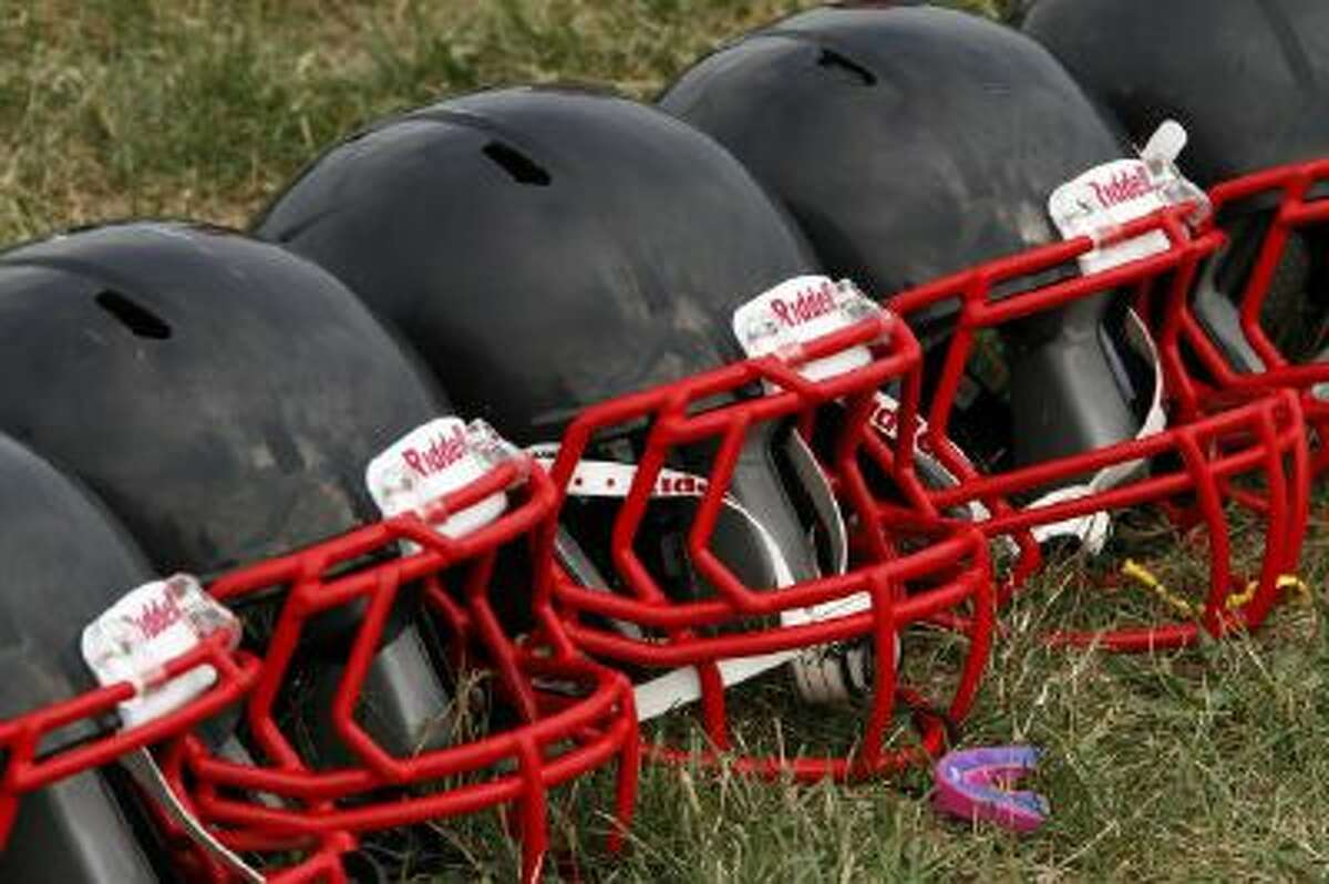 FILE - This Aug. 4, 2012 file photo shows new football helmets that were given to a group of youth football players from the Akron Parents Pee Wee Football League, in Akron, Ohio.