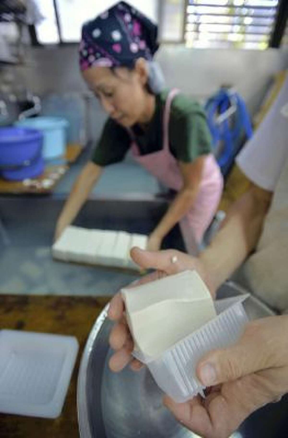 Workers make tofu at a Tokyo company in October.