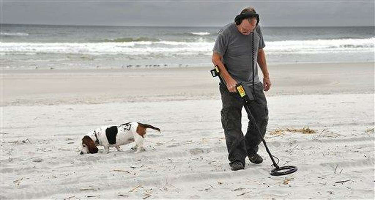 A man searches for buried treasure recently in Jacksonville Beach, Fla. People typically uncover lots of tent pegs, bottle tops, nickels, dimes and quarters. (AP Photo/Florida Times-Union, Bruce Lipsky)