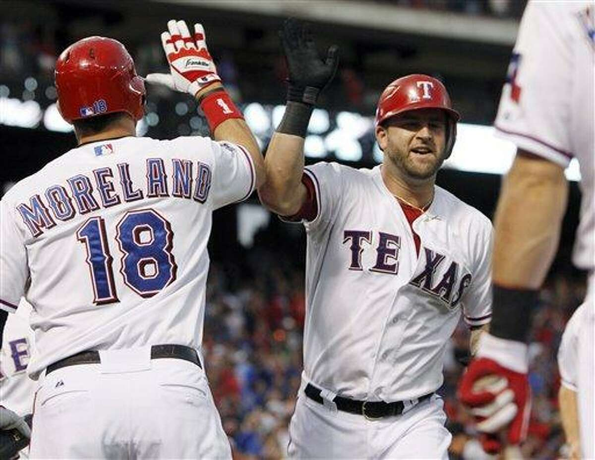 Texas Rangers' Mike Napoli, right, celebrates his home run with Mitch Moreland (18) during the third inning of the second baseball game of a doubleheader against the Los Angeles Angels, Sunday, Sept. 30, 2012, in Arlington, Texas. (AP Photo/LM Otero)