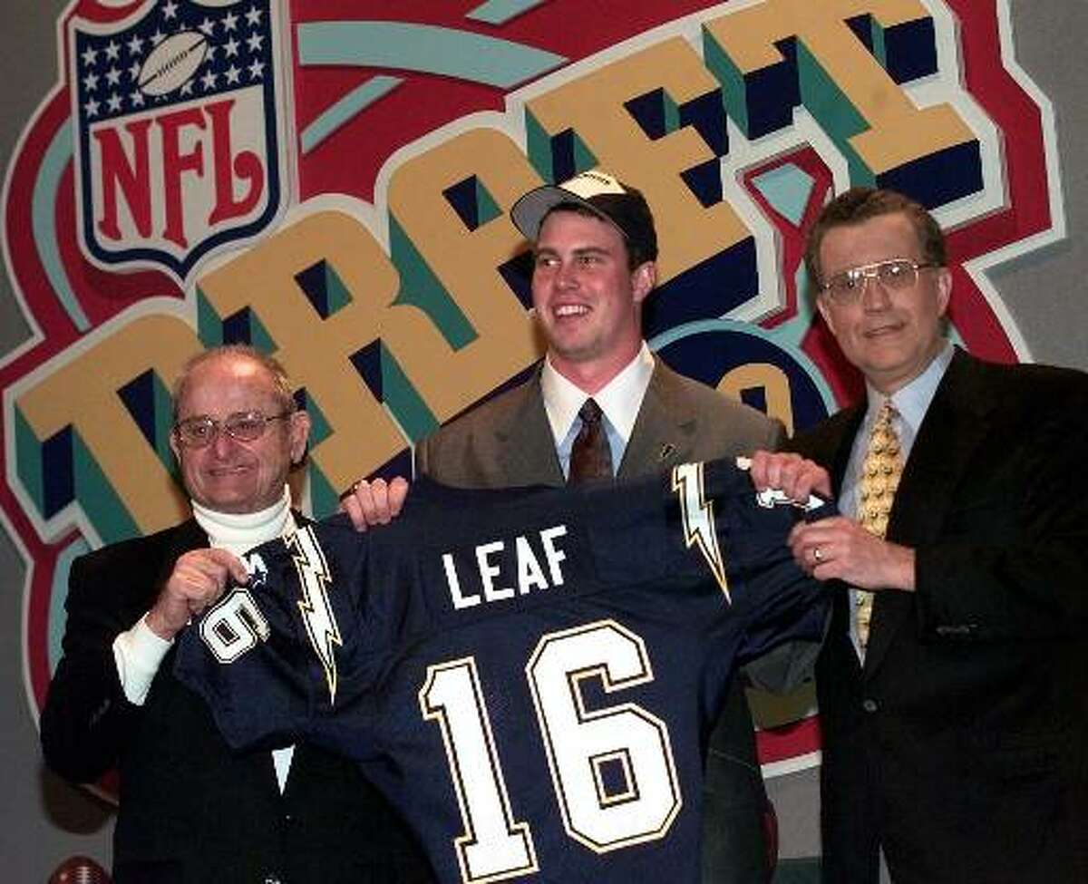 Ryan Leaf, center, of Washington State gets help holding up his San Diego Chargers jersey by Chargers owner Alex Spanos, left, and NFL commissioner Paul Tagliabue after Leaf was chosen by the Chargers as the second pick overall in the NFL draft Saturday, April 18, 1998 in New York. (AP Photo/Mark Lennihan)
