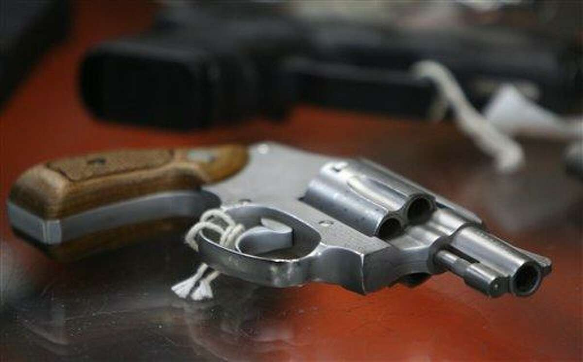 In this June 26, 2008 file photo, a chrome plated revolver rests on top of a glass display case at a gun shop in New York. (AP Photo/Seth Wenig, File)
