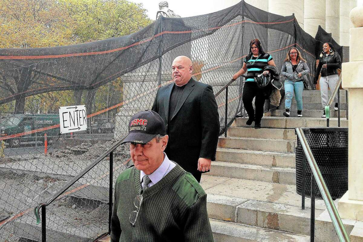 Angelo Appi Jr., rear, follows his father, Angelo Appi Sr., foreground, out of New Haven Superior Court in New haven Wednesday after pleading not guilty to a breach of peace charge.