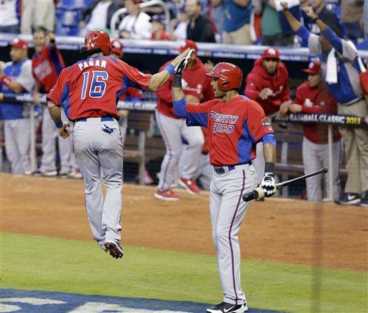 Puerto Rico's Angel Pagan (16) celebrates with on-deck batter Alex Rios after scoring on a single by Mike Aviles during the first inning of the second-round elimination game of the World Baseball Classic against the United States, Friday, March 15, 2013, in Miami. (AP Photo/Wilfredo Lee)